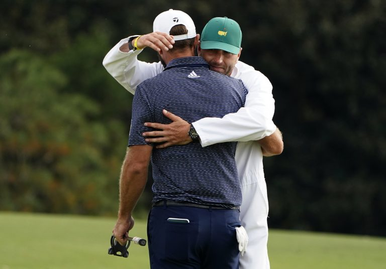 Dustin Johnson is hugged by his brother and caddie Austin