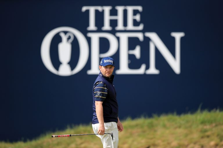 Branden Grace standing in front of The Open signage