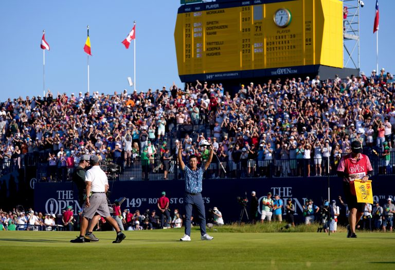 Collin Morikawa celebrates on front of packed grandstands around the 18th green